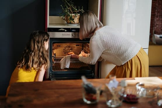 woman in white sweater baking cake